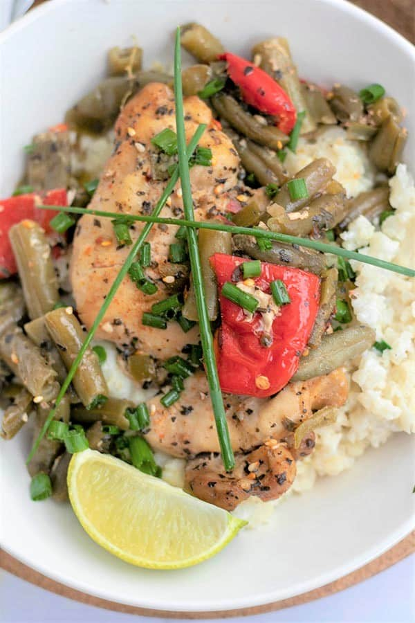 portrait image of slow cooker Thai basil chicken served on a white plate and garnished with lime and chives.