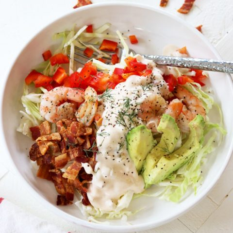 square overhead image of shrimp louie salad in a white bowl.