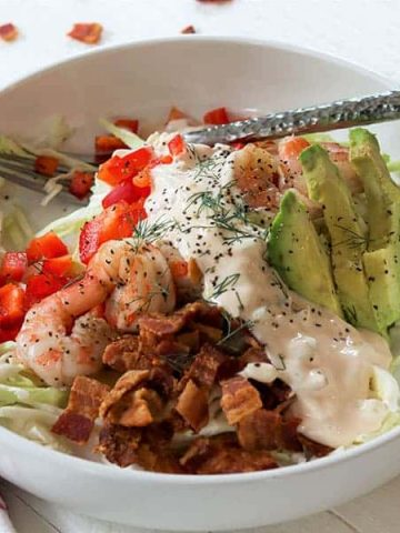 landscape image of shrimp louie salad in a white bowl.