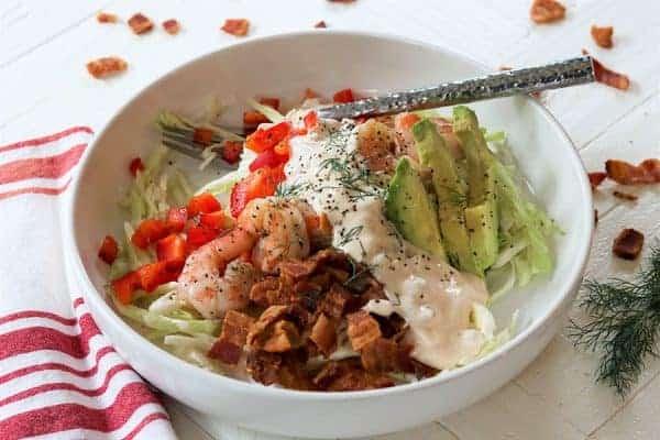 landscape image of shrimp louie salad in a white bowl.