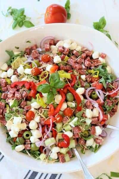 portrait image of antipasto salad presented on a large white platter