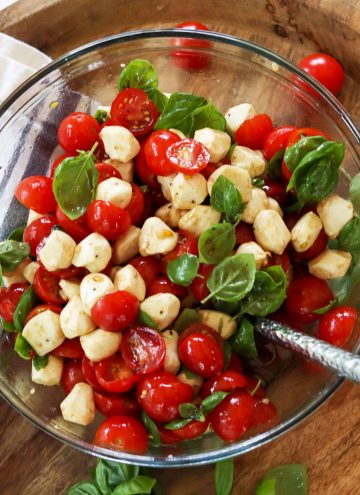 Square image of cherry tomato caprese salad in a clear bowl. Red tomatoes, green basil, and white mozzarella pearls