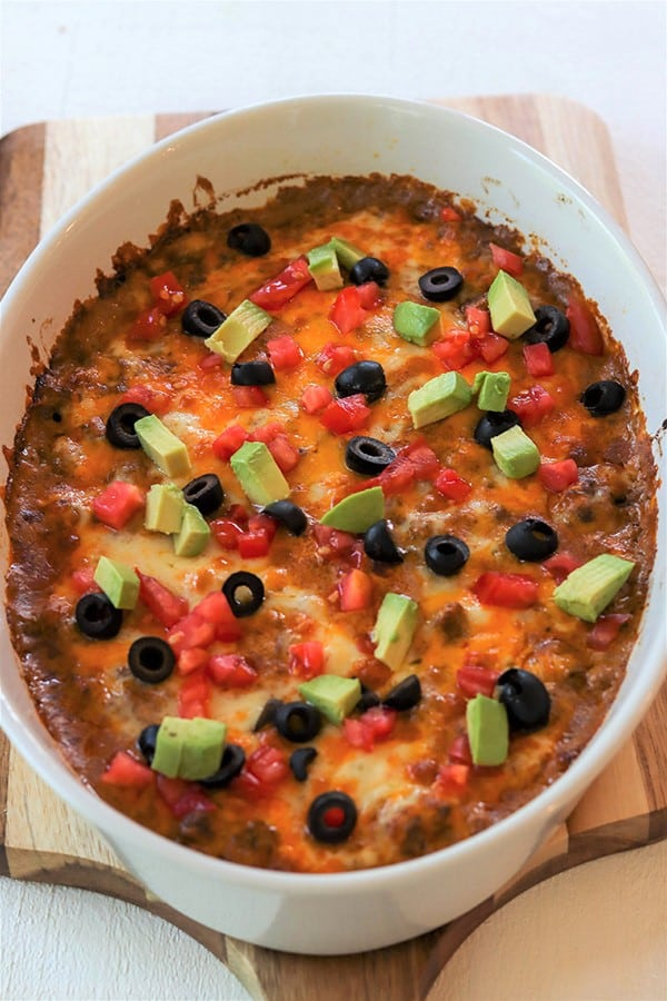 Portrait image of zucchini taco casserole right out of the oven topped with tomato, avocado, and olives.
