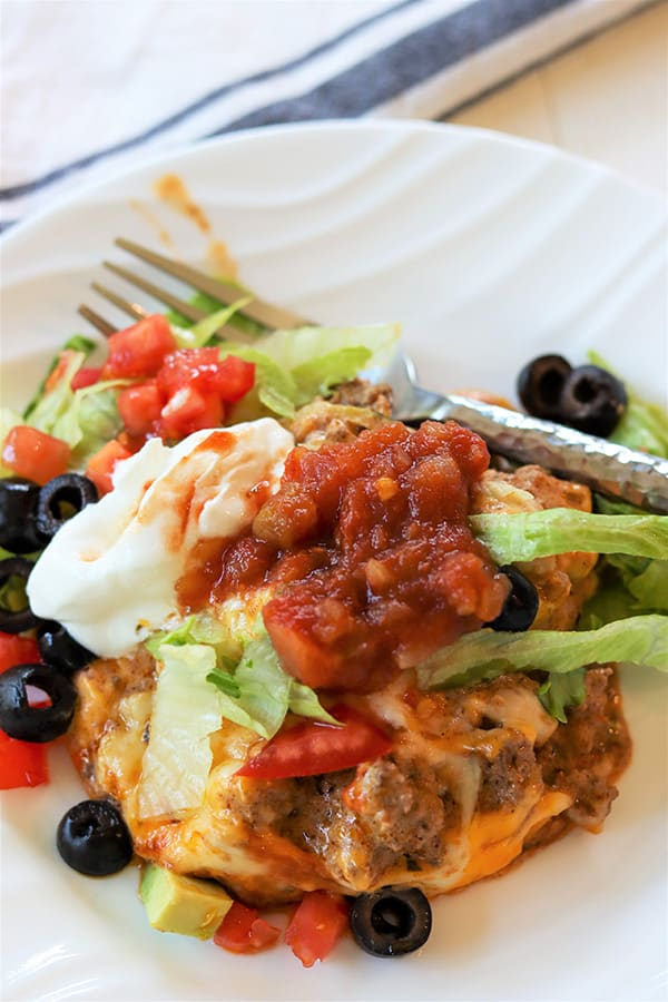 Portrait image of the zucchini ground beef taco casserole on a white plate
