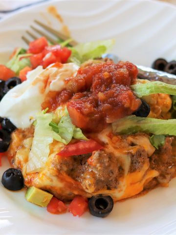 Square image of the zucchini ground beef taco casserole on a white plate