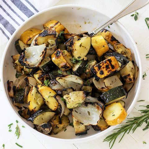 Square image of Herb Marinated Vegetables in a white bowl with spoon