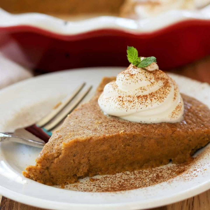 Square image of finished slice of crustless pumpkin pie with full pie plate in the background.