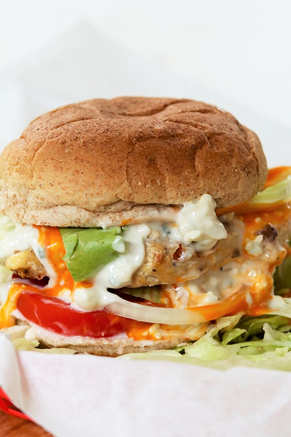 landscape image of buffalo chicken burger on a bun with tomato, lettuce, onion, blue cheese dressing, and buffalo sauce.