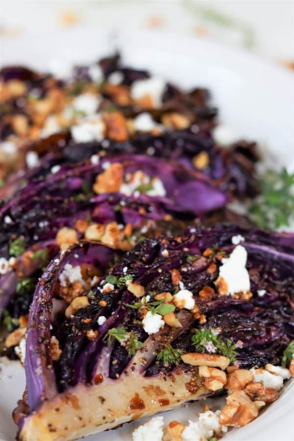 portrait image of roasted red cabbage topped with goat cheese, walnuts, and thyme on a white plate