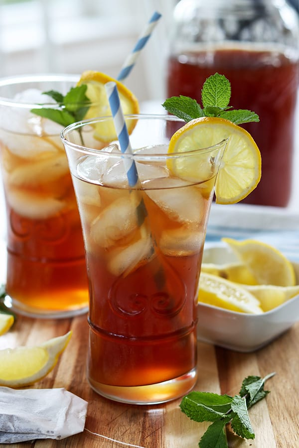 Portrait image of full glasses of refreshing southern sweet tea with a lemon wedge, mint sprig, and colorful blue and white straws.