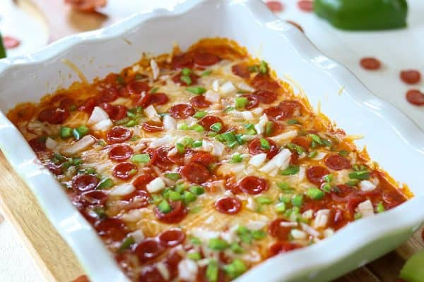 Landscape image of the hot baked dip in a white baking dish, topped with melted cheese, pepperoni, onion, and green pepper.
