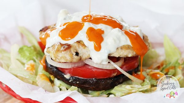 landscape image of buffalo chicken burger served over a grilled portobello mushroom. The low carb version served with lettuce, tomato, onion, blue cheese dressing, and buffalo sauce