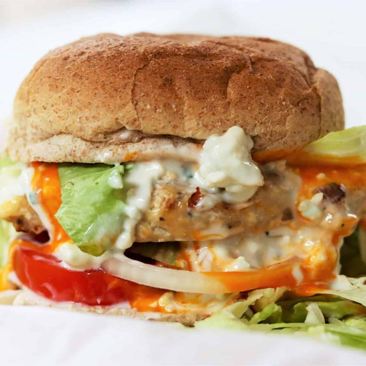 square closeup image of buffalo chicken burger on a bun with tomato, lettuce, onion, blue cheese dressing, and buffalo sauce.