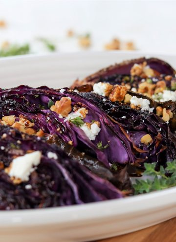 square image of roasted red cabbage topped with goat cheese, walnuts, and thyme on a white plate