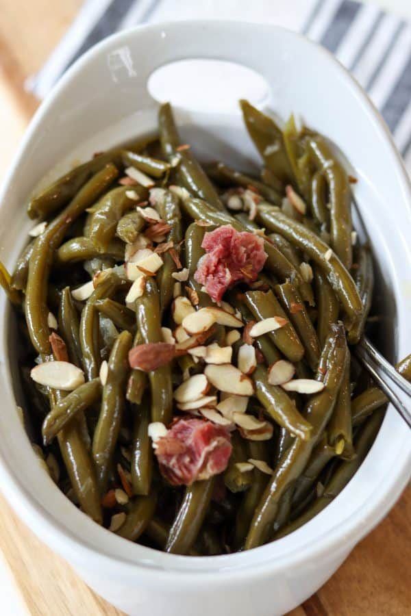 Portrait image of cooked green beans in a white dish topped with sliced almonds and bits of smoked ham