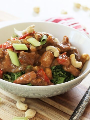 Square image of cashew chicken served in a gray bowl over riced broccoli. A red stripe napkin and silver fork in the background. Scattered cashews and green onion.