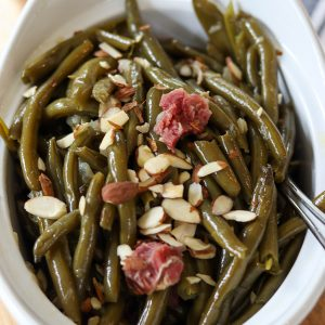 Closeup square image of cooked green beans in a white dish topped with sliced almonds and bits of smoked ham