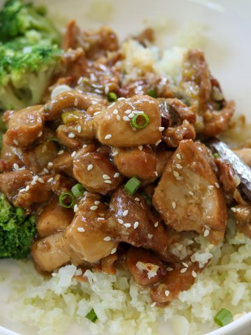 Square closeup image of the sesame chicken served in a white bowl and garnished with sesame seeds and green onion. Served over riced cauliflower and a side of steamed broccoli.