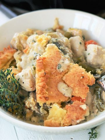 Square closeip image of the chicken pot pie served in a white bowl with chicken, gravy, vegetables, and bits of crust. Garnished with a sprig of thyme. A spoon is ready for you to take a bite.