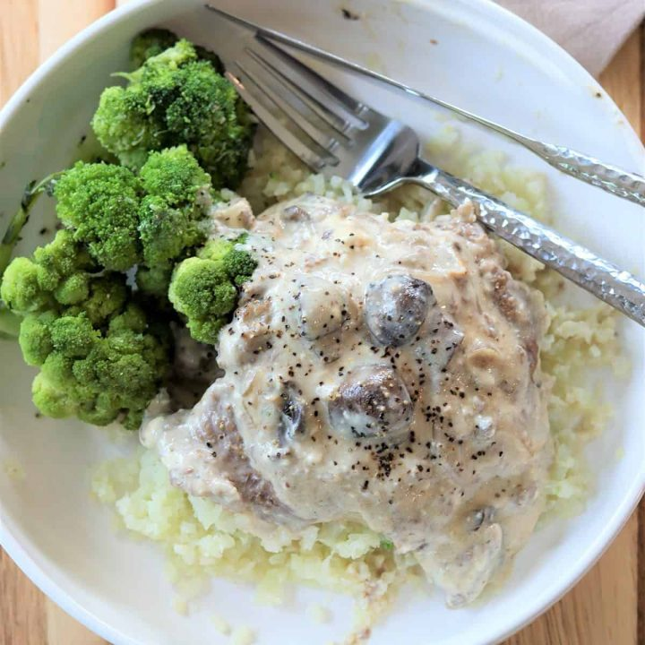 Square top down image of salisbury steak served on a white plate with its rich brown gravy served over riced cauliflower with a side of broccoli. Enjoy!