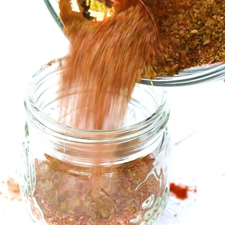 Taco seasoning mix being poured into a jar for later use.