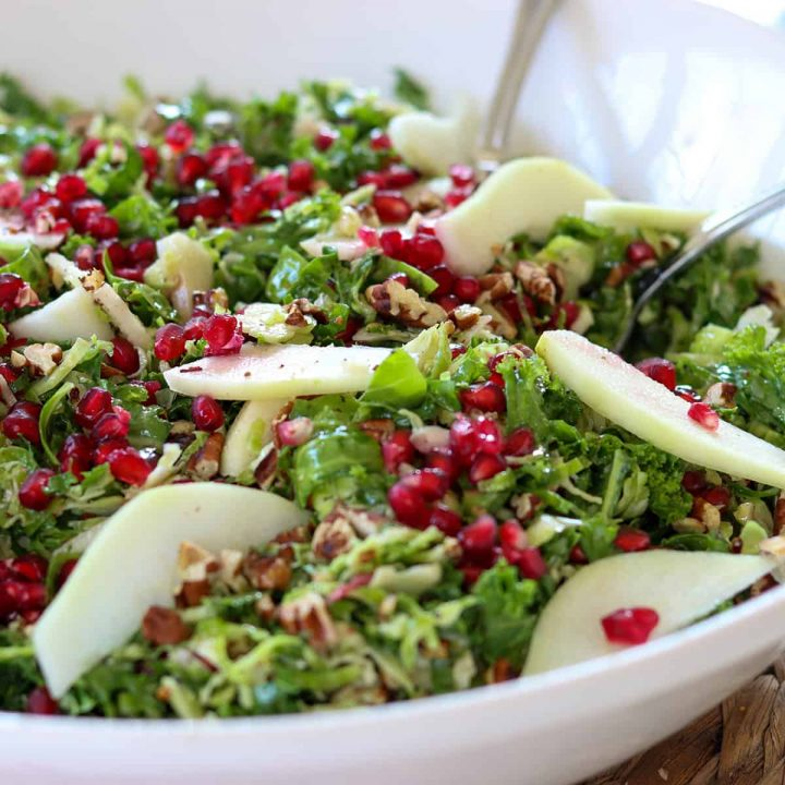 Square closeup image of the completed kale and brussel sprout salad in a white bowl.