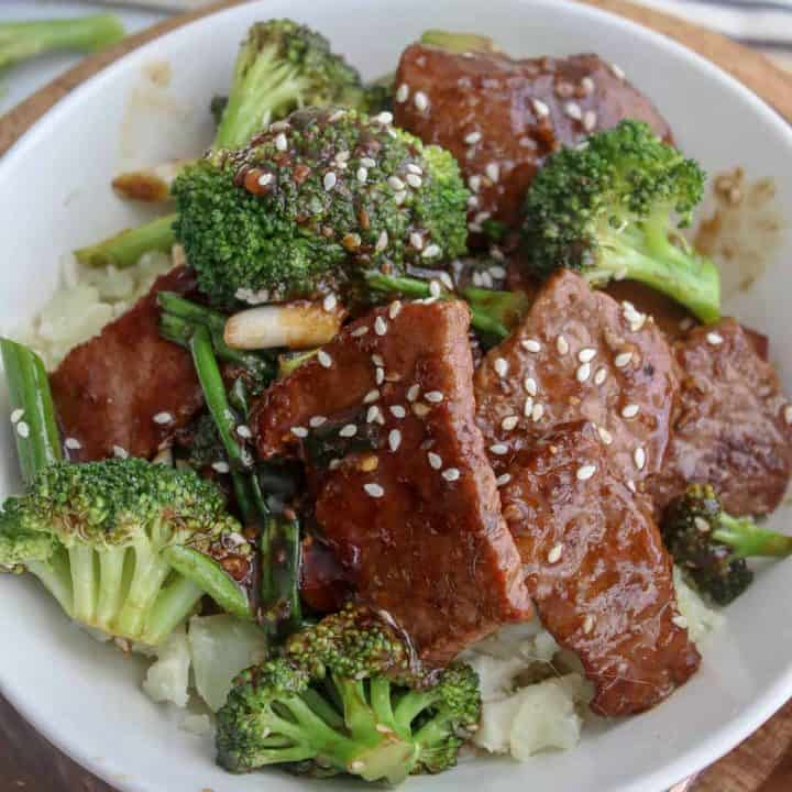 square closeup image of mongolian beef and broccoli served in a white bowl and garnished with sesame seeds.