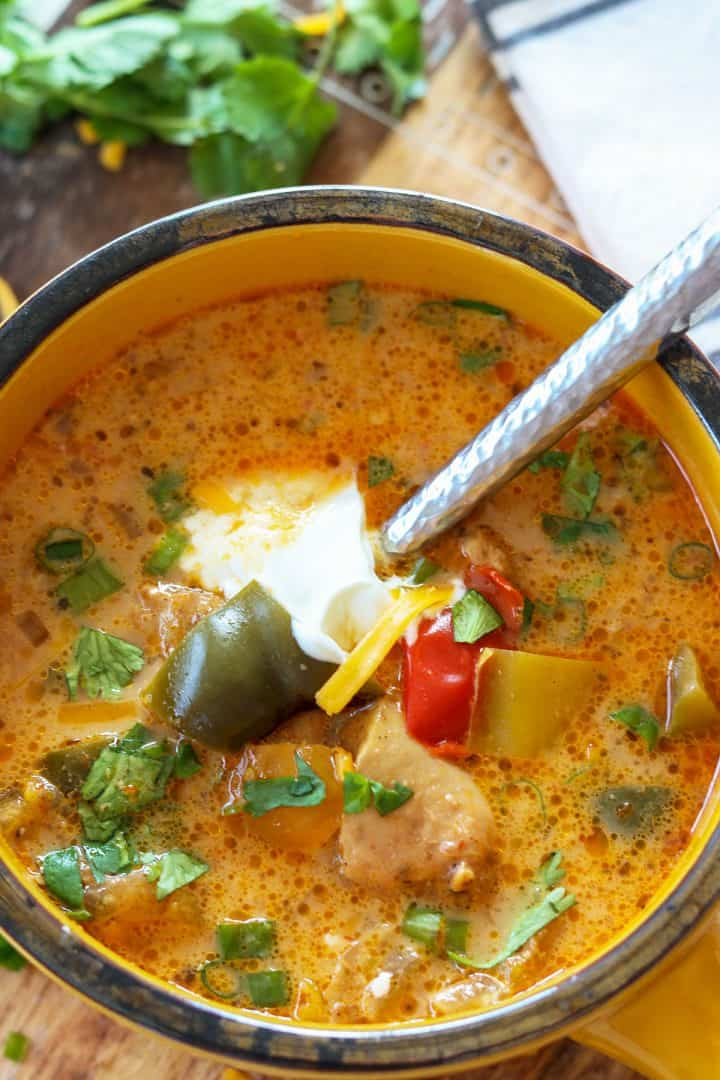 Portrait image of chicken fajita soup served in a yellow bowl and garnished with sour cream, cilantro, and green onion. Chunks of chicken and green, yellow, and red peppers float in the creamy broth.