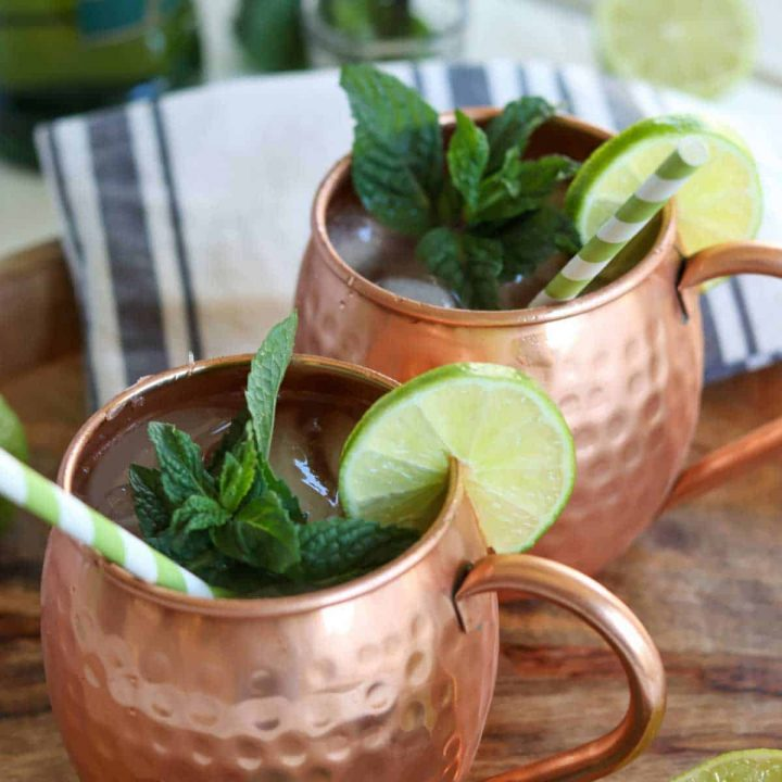 square closeup image of two irish mule cocktails served in a copper mug and garnished with lime slices, mint leaves, and straws.