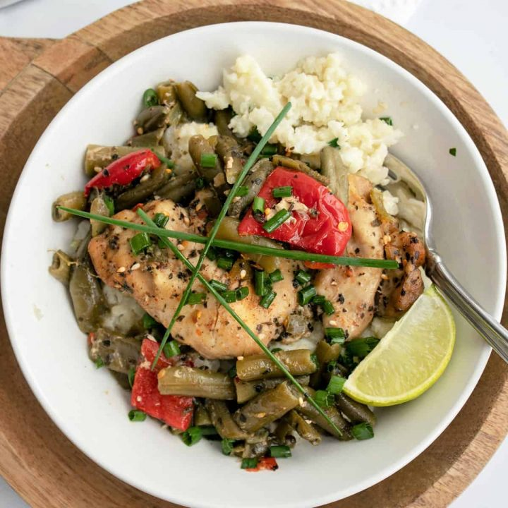 Thai basil chicken served over riced cauliflower on a white plate with a slice of lime and garnished with chives.