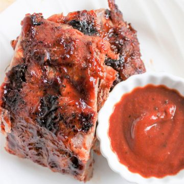 Closeup image of juicy grilled ribs served on a white plate with a side of barbeque sauce for dipping.