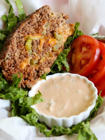 Square closeup image of meatloaf served in a fast food basket with a side of homemade big mac sauce. Served on a bed of lettuce with a side of tomatoes.