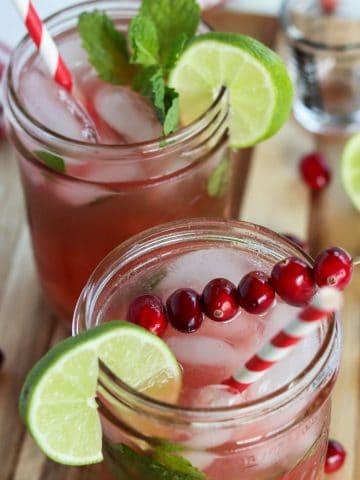 2 cranberry mojitos served in mason jars and garnished with lime, mint, and cranberries.