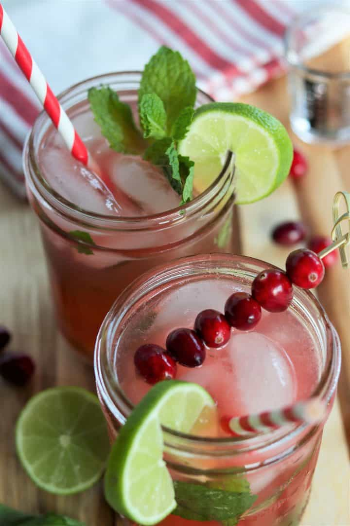 Festive red cranberry mojitos served in a mason jar with red and white straws, and garnished with lime slices, sprigs of mint, and cranberries.