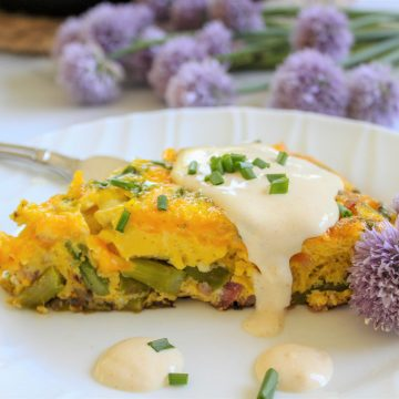 Eggs benedict frittat is served on a white plate and drizzled with hollandaise sauce and garnished with chive blossoms and chives.