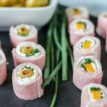 closeup view of ham rollups. Some are stuffed with cheese, others with olives and chives.