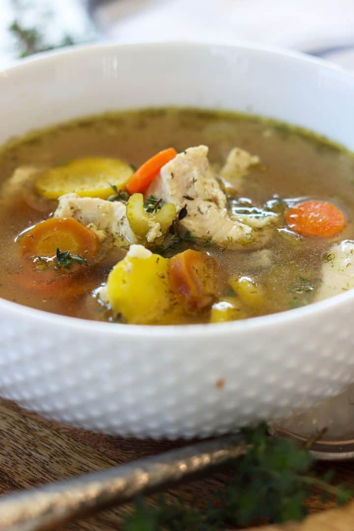 Chicken served in a white bowl. Soup is full of tender chicken and vegetables like colorful carrots.