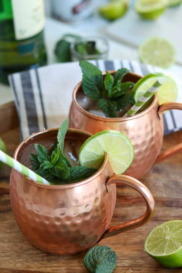 two Irish mules served in copper mugs garnished with lime, mint, and green and white strip straws.