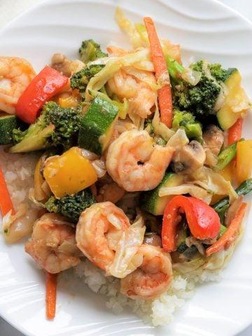 closeup image of shrimp stir fry served on a white plate over cauliflower rice