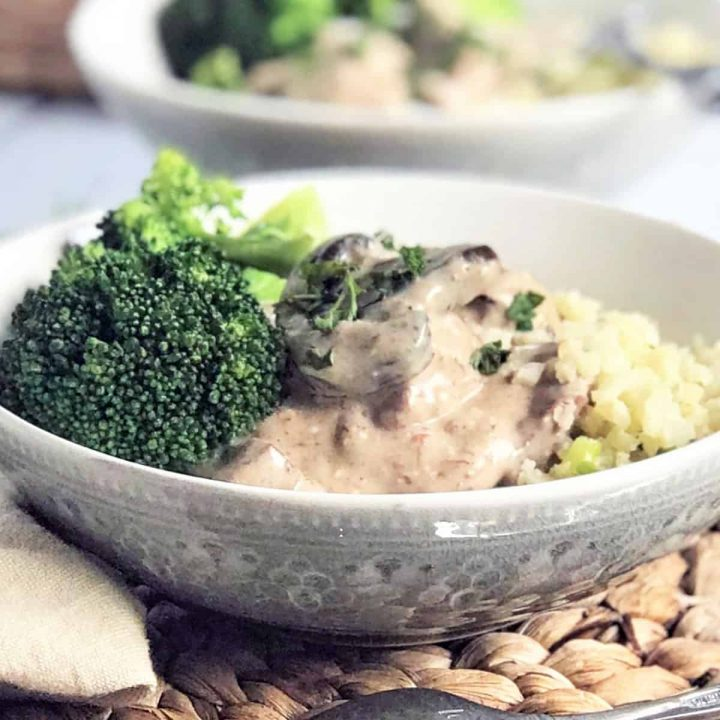 Featured image of beef stroganoff served in a gray bowl with a side of broccoli and garnished with parsley.