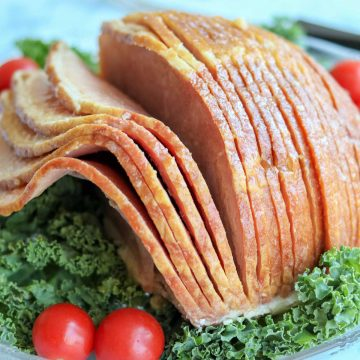 Closeup view of ham sliced and sitting on a bed of lettuce and decorated with cherry tomatoes.