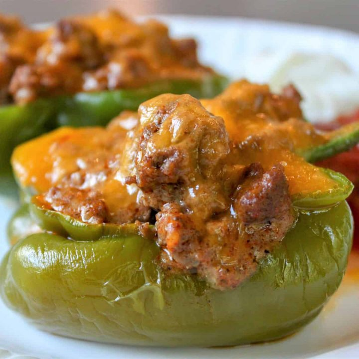 featured image of of fully baked taco stuffed pepper with melted cheese and filling spilling over the side.