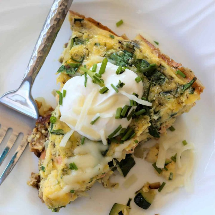 Smoked salmon frittata feature image. Top down view of a slice of frittata served on a white plate and garnished with sour cream, chives, and extra cheese.