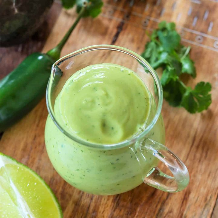Square feature image of a top down view of the vegan avocado dressing served in a clear glass container. The dressing is bright green and an avocado, jalapeno, and lime are laying around it.