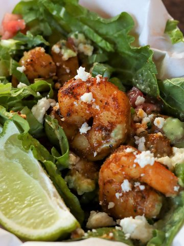 Feature image with a closeup of shrimp served in lettuce and garnished with a wedge of lime, cheese, and dressing