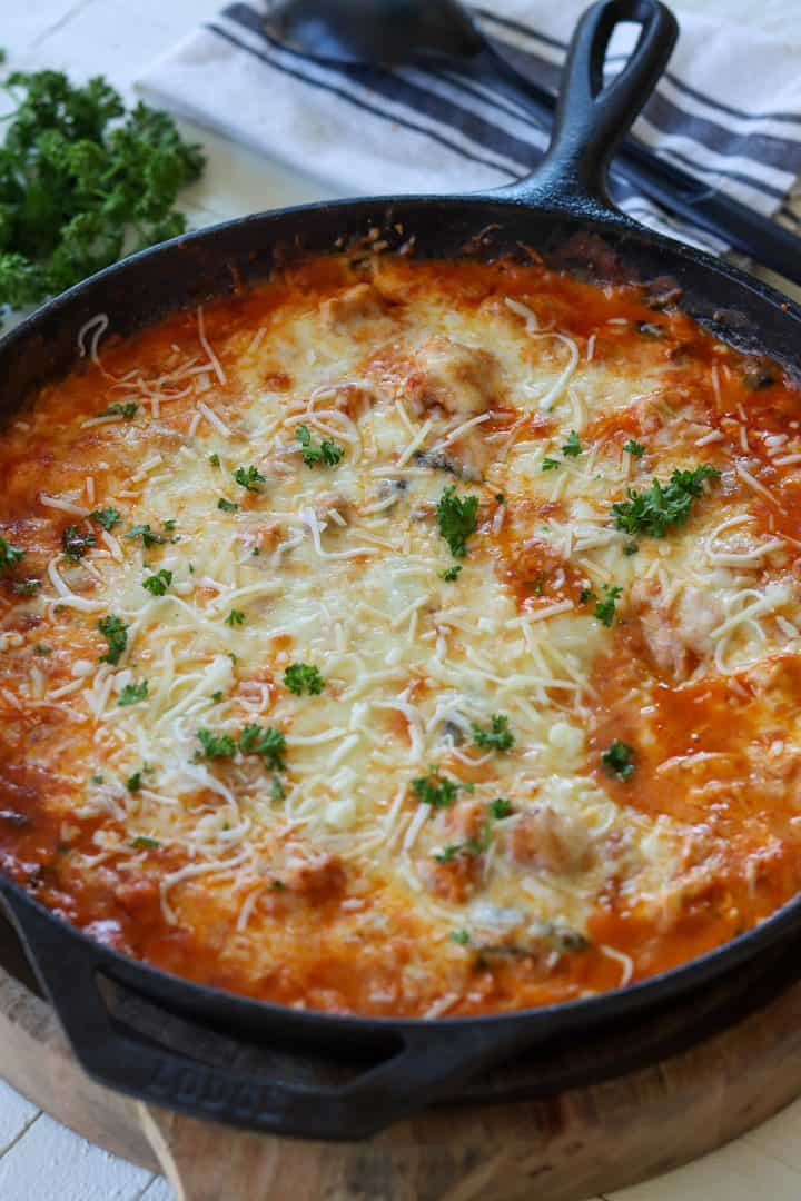portrait image of Parmesan Chicken Casserole just out of the oven and ready to serve. Casserole was baked in a cast iron skillet and garnished with parmesan and fresh parsley.