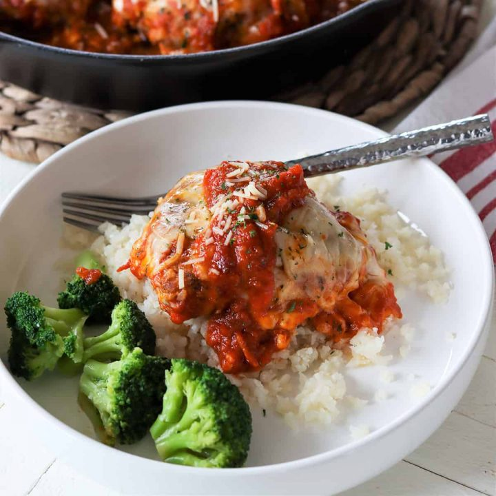 feature image of chicken parmesan casserole served on a white plate with a side of steamed broccoli.