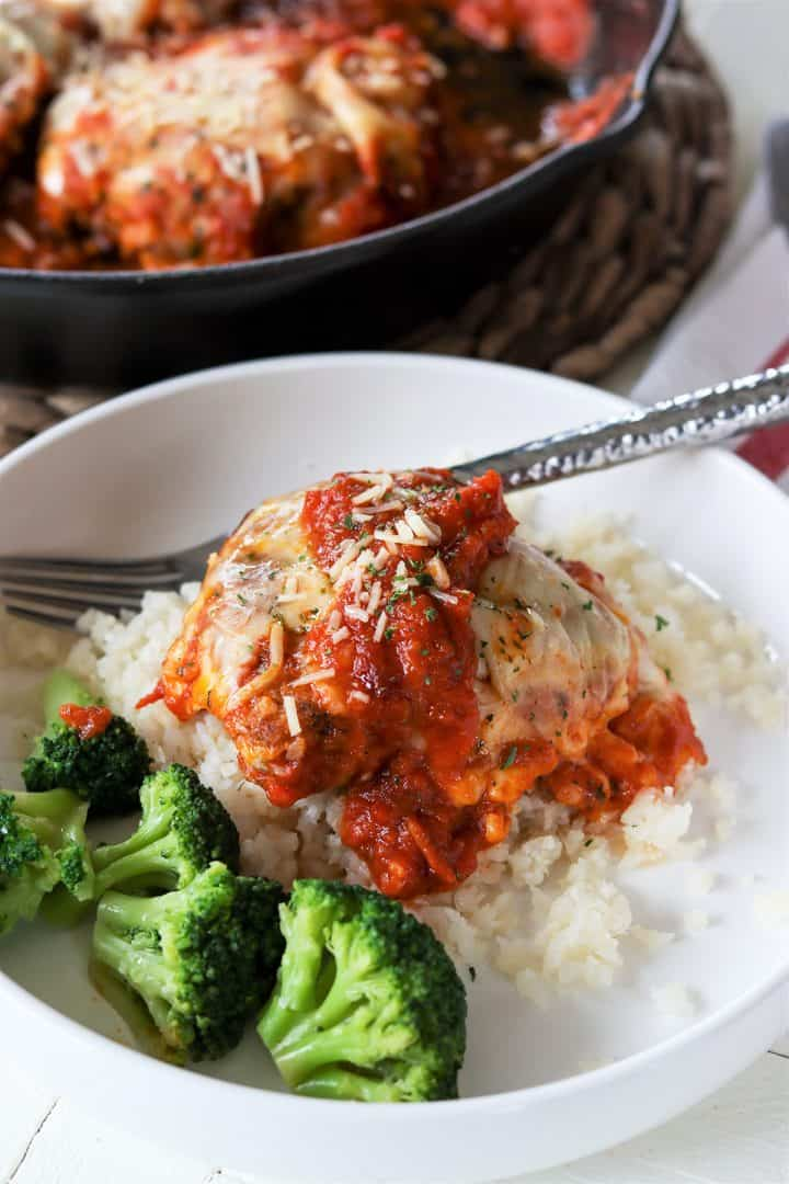 One serving of keto chicken parmesan is served over rice cauliflower with a side of broccoli. Extra marinara is drizzled over the top with a spinkle of parmesan cheese.