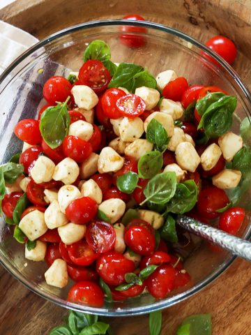 Square feature image with a top down view of cherry tomato caprese salad served in a glass bowl with tiny mozzarella pearls, cherry tomatoes, and fresh baby basil leaves tossed in a viniagrette dressing.