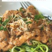 Pinterest image of low carb chicken in tomato basil cream sauce served over zucchini noodles and garnished with parmesan cheese and parsley.